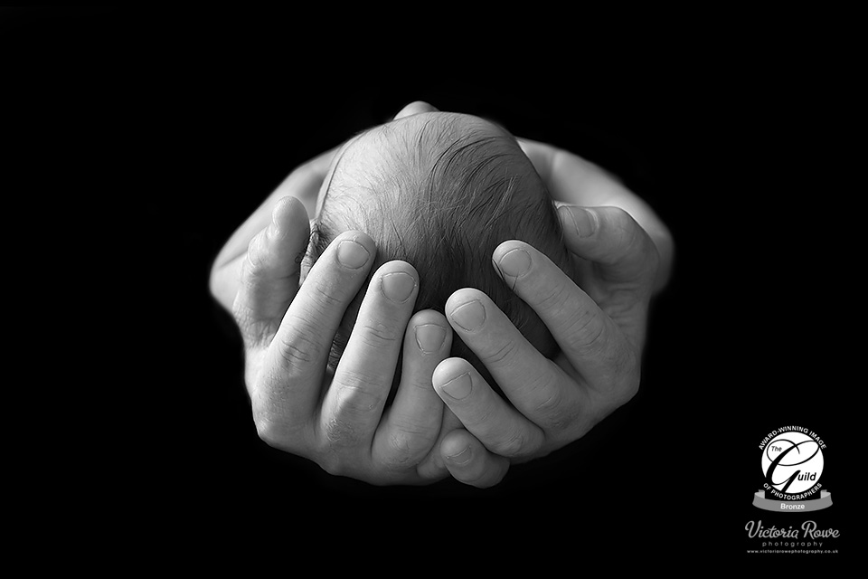 Newborn baby girl held safely in her father's hands