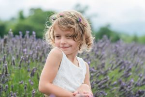 Little girl soaks up the scent of lavender on a beautiful summer's day