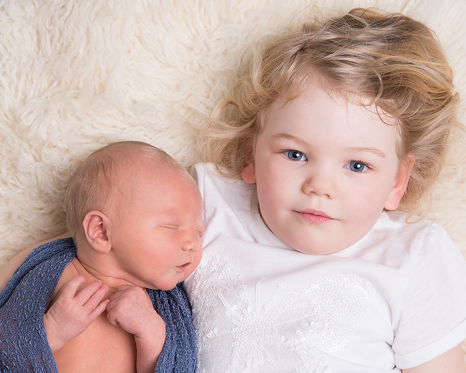 A big sister cuddles up with her newborn baby brother