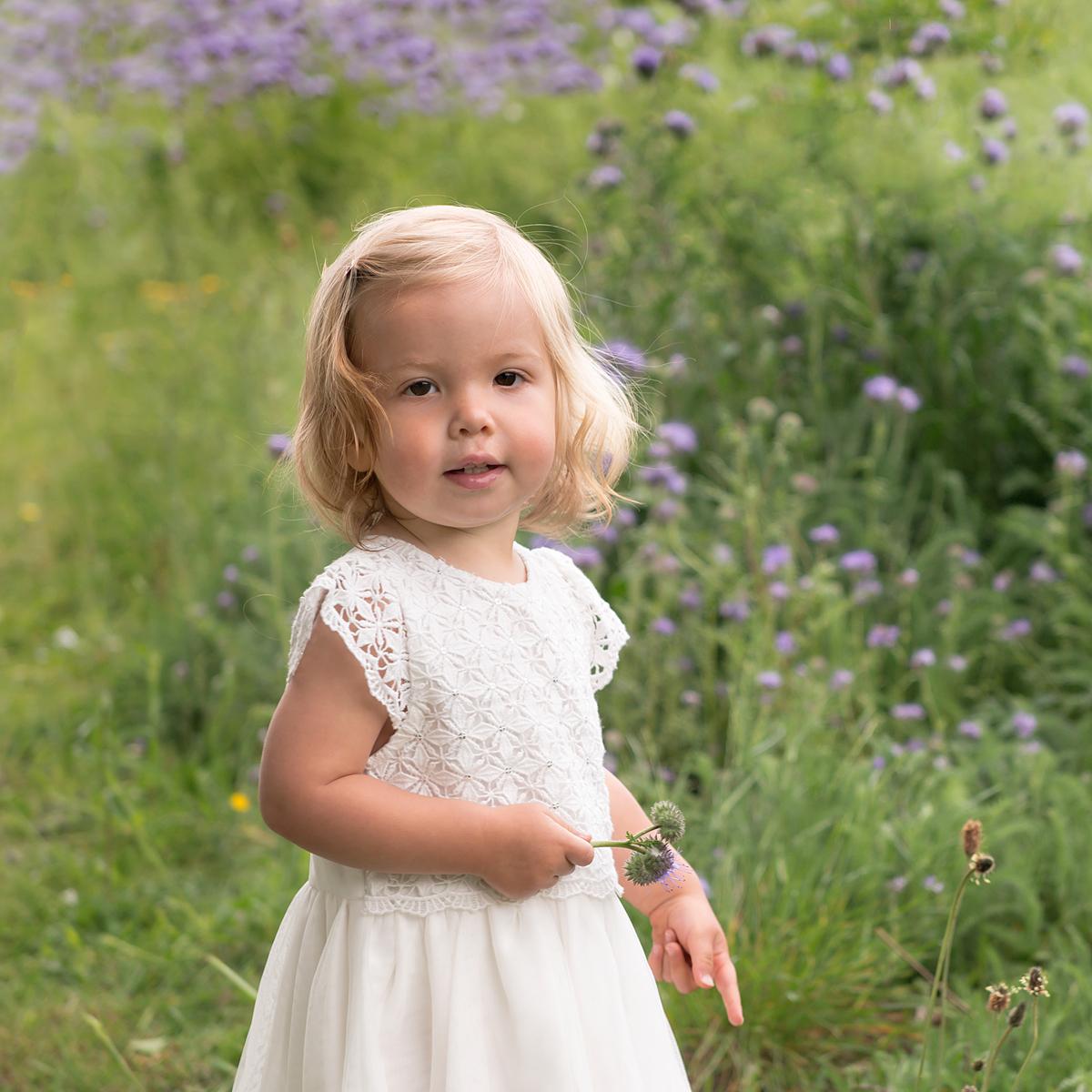 Little girl holds a flower in a field of wildflowers in Crane Park