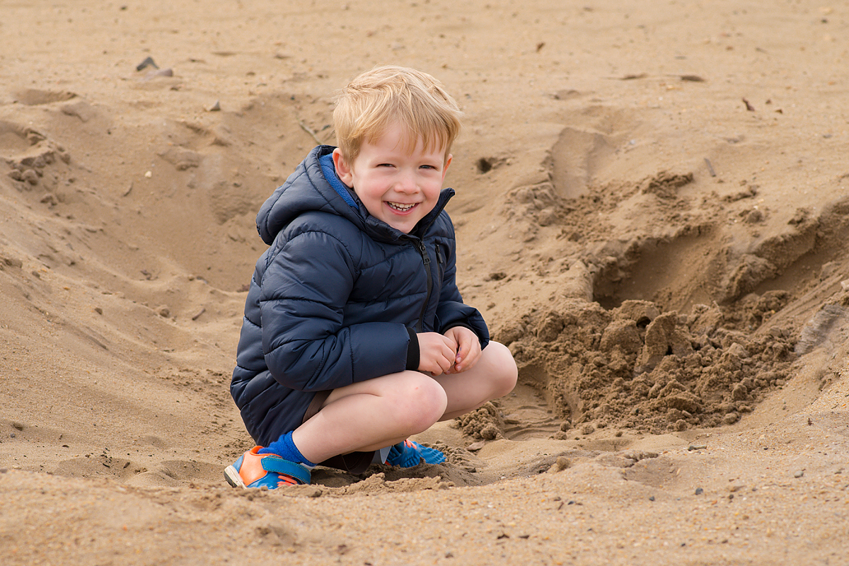 Little boy crouching on the sand at Frensham Ponds